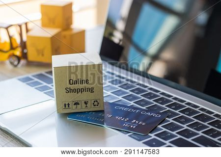 Cardboard Box With Text Online Shopping And Symbols And Mock Up Of Credit Card On Laptop Keyboard. L