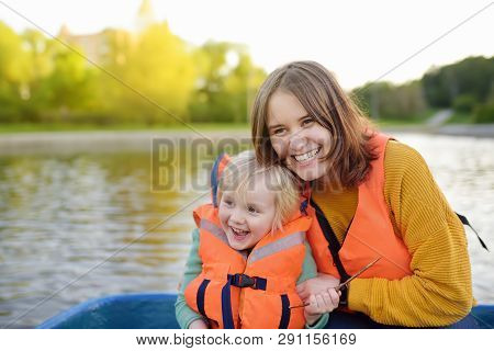 Young Mother And Little Son Boating On A River Or Pond At Sunny Summer Day. Quality Family Time Toge
