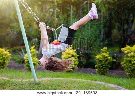 Child Swinging On Playground. Kids Swing.