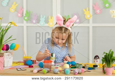 Little Child Girl With Easter Bunny Ears Painting Easter Eggs At Home. Adorable Child Prepare For Ea