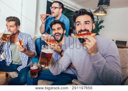 Group Of Four Male Friends Drinking Beer And Eating Pizza At Home.