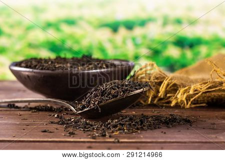 Lot Of Pieces Of Dry Black Tea Earl Grey In A Grey Ceramic Bowl On Jute Cloth With Silver Spoon Gree