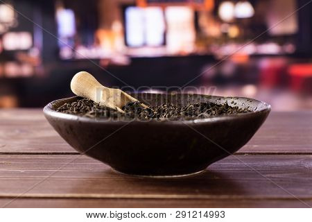 Lot Of Pieces Of Dry Black Tea Earl Grey In A Grey Ceramic Bowl With Wooden Scoop With Restaurant In