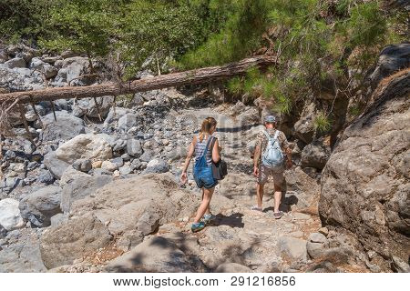 Two Tourists, A Young Girl And A Man Walking Along The Trail In The Samaria Gorge On The Island Of C