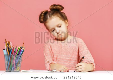 A Cute Little Baby Girl Is Sitting At The Table And Drawing With Enthusiasm. Pink Background Close-u