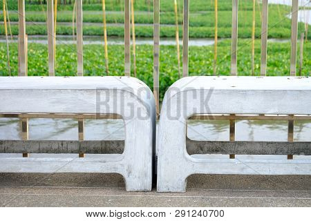 A pair of white stone benches on cement bridge at the port with steel handrails and river view background poster