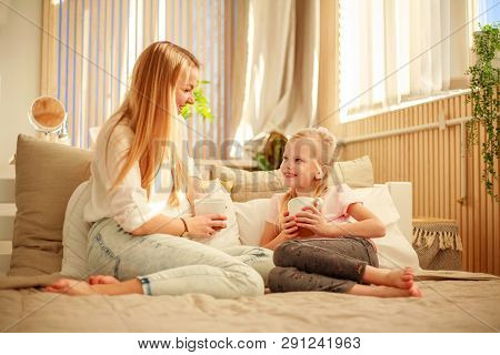 Mother And Daughter With A Cup Of Tea At Home Talking On The Bed, Happy Family Lifestyle