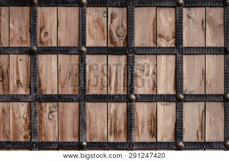 Wooden Texture Framed By Metal Forged Strips. Stylization Of The Ancient Gate Of The Castle.