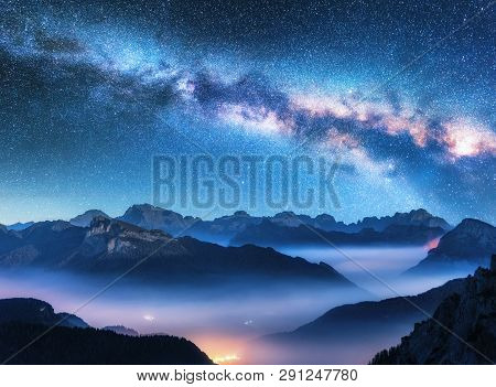 Milky Way Above Mountains In Fog At Night In Summer. Landscape With Alpine Mountain Valley, Low Clou