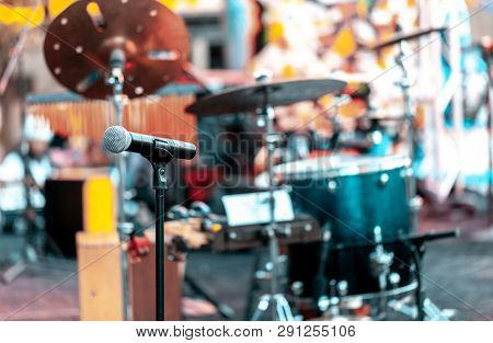 Microphone With Drums And Other Musical Instruments On A Outdoor Stage For Performing Music. Focus O