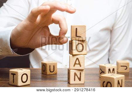 A Businessman Is Trying To Take Down A Tower Of Cubes With The Word Loan. Refusal To Pay Loans. Simp