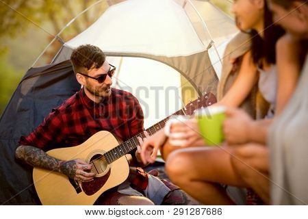 hipster man with guitar on camping trip with friends