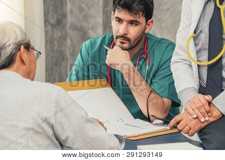 Male Doctor Team Talking To Senior Patient Visit