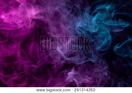 Dense Multicolored Smoke Of   Blue And Pink Colors On A Black Isolated Background. Background Of Smo