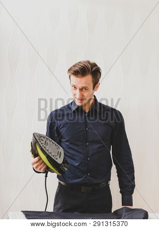 Single man is ironing shirt on board, at home. Housework concept.