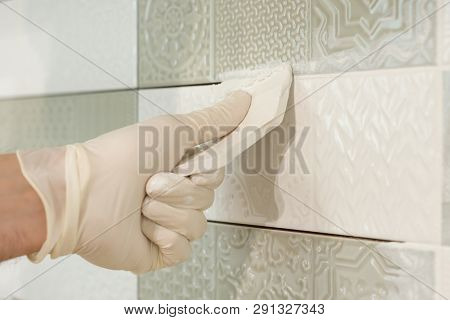 Closeup Of Tiler Hand Rubbing Tile, Installing And Grouting Decorative Finishes In Environments With