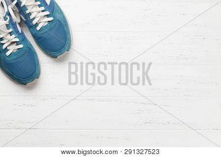 Fitness concept. Sneakers on wooden background. Top view with space for your running shedule text