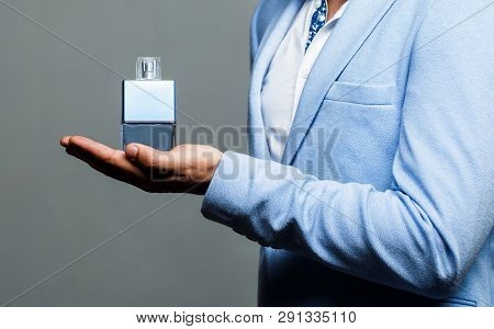 Masculine Perfume, Bearded Man In A Suit. Man Perfume, Fragrance. Male Holding Up Bottle Of Perfume.