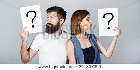 Portrait Of Couple Holding Paper Question Mark. Couple Thinking About Something. Confused Couples Wi