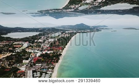 Aerial View Of The Coastal Small Town And The Turquoise Sea With A Horizon Mirror Effect. Beautiful