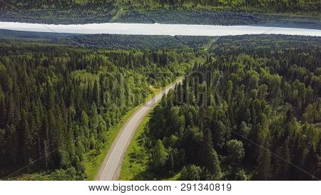 Aerial View Of A Curved Empty Road In A Forest In A Summer Day, Mirror Horizon Effect. Green Forest