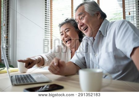 Happy Asian Senior Couple Having Fun With A Laptop Computer Technology.
