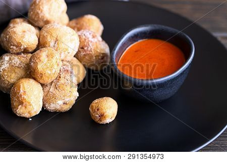 Famous Canary Islands dish, Papas Arrugadas (wrinkly potatoes with salt) and Mojo picon (red  spicy sauce) on wood table in local restaurant. poster
