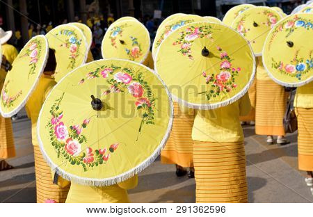 Northern Lanna Thai Woman Hold Yellow Traditional Umbrella That Paint With Flowery Pattern For Prote