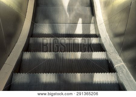 Shadows Of Two Persons On An Escalator