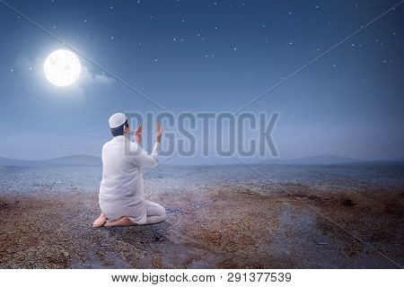 Rear View Of Asian Muslim Man Sitting In Pray Position While Raised Hands And Praying On The Sand Du