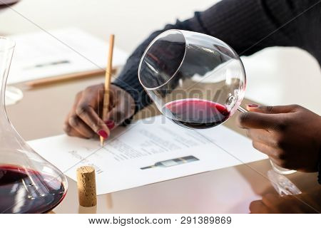 Close Up Detail Of African Hands Holding Red Wine Glass.wine Enthusiast  Evaluating Red Wine At Wine
