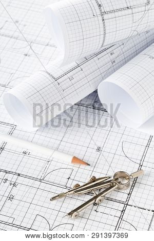 Rolls Of Architectural Blueprint House Building Plans On Blueprint Background On Table With Pencil A