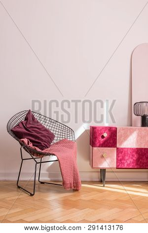 Trendy Metal Armchair With Burgundy Pillow And Pink Blanket Next To Classy Suede Covered Cabinet, Re