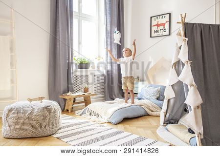 Boy Playing With A Toy In A Cozy Child Playroom Interior