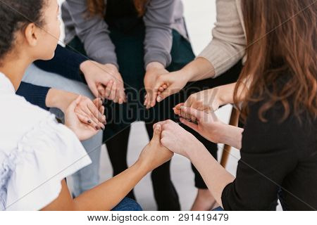 Closeup Of Group Of Females Sitting In Circle Holding Hands During Support Group Meeting