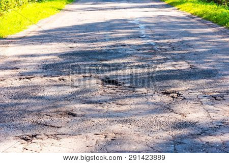 Broken Empty Asphalt Country Road Surrounded By Trees In Sunny Summer Day. Road With Holes In The Gr
