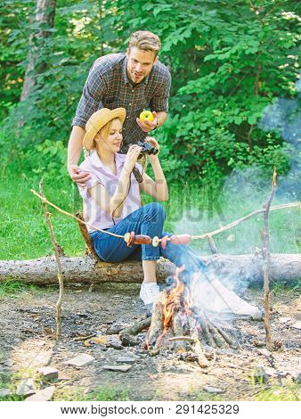 Observing nature concept. Couple ornithologists expedition in forest. Couple enjoy hike in forest observing nature. Ornithology interesting occupation. Woman and man looking binoculars near bonfire poster