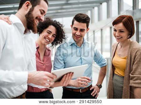 Group Of Young Busiensspeople With Tablet Standing In Office, Talking.