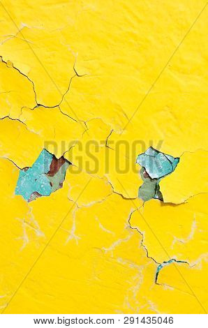 Texture background - yellow and blue peeling paint on the old concrete surface, close up of peeling paint texture on the old concrete texture background. Grunge texture surface with yellow peeling paint