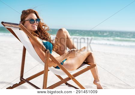 Happy young woman relaxing on deck chair at beach while looking at camera. Mature woman with red hair wearing sunglasses and blue bikini enjoying vacation at beach. Sunbathing and relaxing at sea.