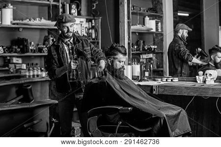 Barber with hairdryer works on hairstyle for bearded man barbershop background. Barber with hairdryer drying hair of client. Hipster lifestyle concept. Hipster bearded client getting hairstyle poster