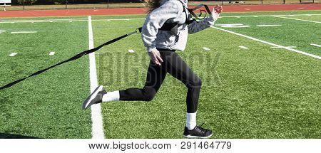 Side View Of A Female High Shool Runner Sprinting On A Green Turf Field While Pulling A Resistance S