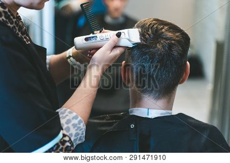 Hairdresser Cutting Man's Hair With Electric Trimmer