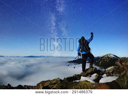 Back View Of Tourist Hiker With Backpack And Trekking Poles Standing With Raised Arm On Huge Rocks O