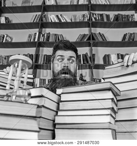 Man On Surprised Face Between Piles Of Books, While Studying In Library, Bookshelves On Background.