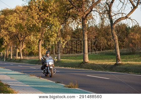 Bearded Biker In Sunglasses, Helmet And Black Leather Clothing Riding Cruiser Powerful Motorcycle Al