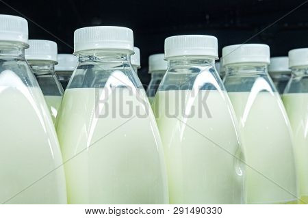 Bottles Of Milk Close Up, Show On A Shelf For Sale In A Supermarket