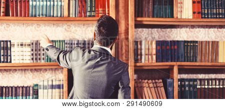 Man Takes Book From Bookcase. Student Stands In Library And Choose Book. Guy In Smart Suit Reads Nea