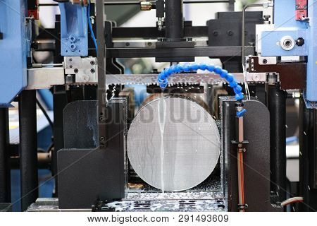 The industrial sawing machine cutting the steel rod with coolant fluid.The band saw machine cutting raw metals rods the with the coolant fluid. poster