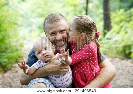 Devoted Father Hugging His Son And Daughter, Enjoying The Outdoor. Family Love And Bonding, Active L